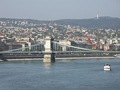 """The Buda-side of the Széchenyi Chain Bridge (""""Lánchíd""""), as well as there are houses on the Buda Hills and a TV-tower on the Hármashatár Hill in the background - Budapešť, Maďarsko"""