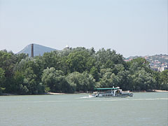 """Small riverboat on the Danube River, in front of the Óbuda Island (also known as """"Hajógyár Island"""" or """"Shipyard Island""""), viewed from the """"Népsziget"""" (""""People's Island"""") - Budapešť, Maďarsko"""
