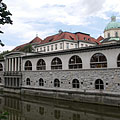 "The so-called Plečnik's arcades building complex by the river, and some distance away the roof of the covered market hall (""Pokrita tržnica"") and the dome of the Cathedral of St. Nicholas can be seen - Ljubljana, Slovénie"