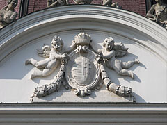 Stone carved coat of arms of Hungary with the crown and two angels or putti, on the main facade of the palace - Gödöllő, Угорщина