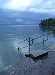 One of the stairs of the free beach, in the distance storm clouds of a supercell are gathering over the lake - Balatonföldvár, Ungarn