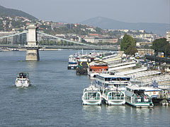 """Berthed riverboats at the Danube bank in Pest downtown, and a little farther the Széchenyi Chain Bridge (""""Lánchíd"""") - Budapest, Ungarn"""