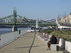 """Riverside promenade by the Danube in Ferencváros (9th district), and the Liberty Bridge (""""Szabadság híd"""") in the background - Budapest, Ungarn"""