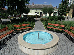 Blue round fountain pool in the small park at the central building block of the main square - Nagykőrös, Ungarn