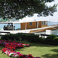 A fishing boat is berthed in the harbor, and a small park is in in front of it - Slano, Kroatien
