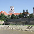 "Details of the castle wall, as well as the Rába River and the towers of the Bishop's Caste (""Püspökvár"") and the Basilica, viewed from the Radó Island - Győr, Ungari"