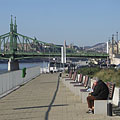 "Riverside promenade by the Danube in Ferencváros (9th district), and the Liberty Bridge (""Szabadság híd"") in the background - Budapest, Ungarn"