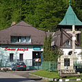 The main square of Újhuta, in the middle of the square there is a belfry, a crucifix and a World War II memorial, as well as in the background it is the Emese Pension - Háromhuta, Ungarn