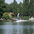 Holiday homes of the Barbakán Street on the other side of the Danube, and a motorboat on the river, viewed from the Csepel Island - Ráckeve, Ungarn