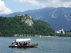 "A ""pletna"", traditional rowing boat on the lake, in th backround it is the Bled Castle and the neo-gothic Parish Church of St. Martin - Bled, Slovenia"