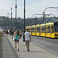 Passers-by and a yellow tram on the Margaret Bridge (looking to the direction of Buda) - Budapest, Hungary