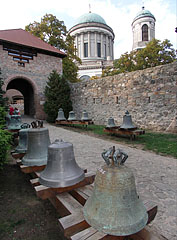 Exhibited bells in the castle, and farther the dome and the belltower of Esztergom Basilica can be seen. - Esztergom, Hungary