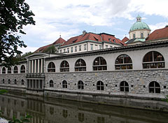"The so-called Plečnik's arcades building complex by the river, and some distance away the roof of the covered market hall (""Pokrita tržnica"") and the dome of the Cathedral of St. Nicholas can be seen - Ljubljana, Slovenia"