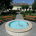 Blue round fountain pool in the small park at the central building block of the main square - Nagykőrös, Hungary