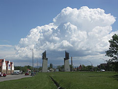 The Tokaj-Hegyalja World Heritage Gate on the main road, with gathering cumulus clouds above it - Szerencs, Hungary