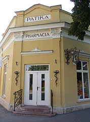 "Entrance of the Tóvárosi Pharmacy (""Tóvárosi Gyógyszertár"") on the corner of the yellow building - Tata, Hungary"